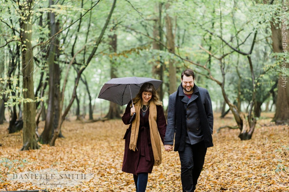 couple walking through woods with umbrella