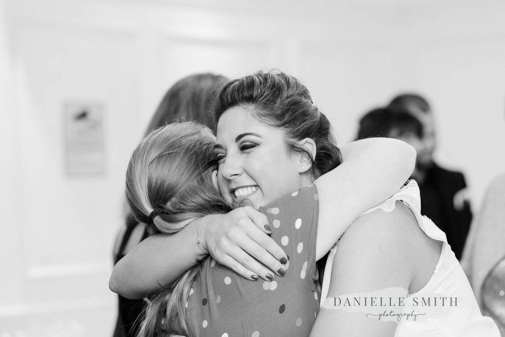 bride hugging wedding guest - orsett hall wedding photography