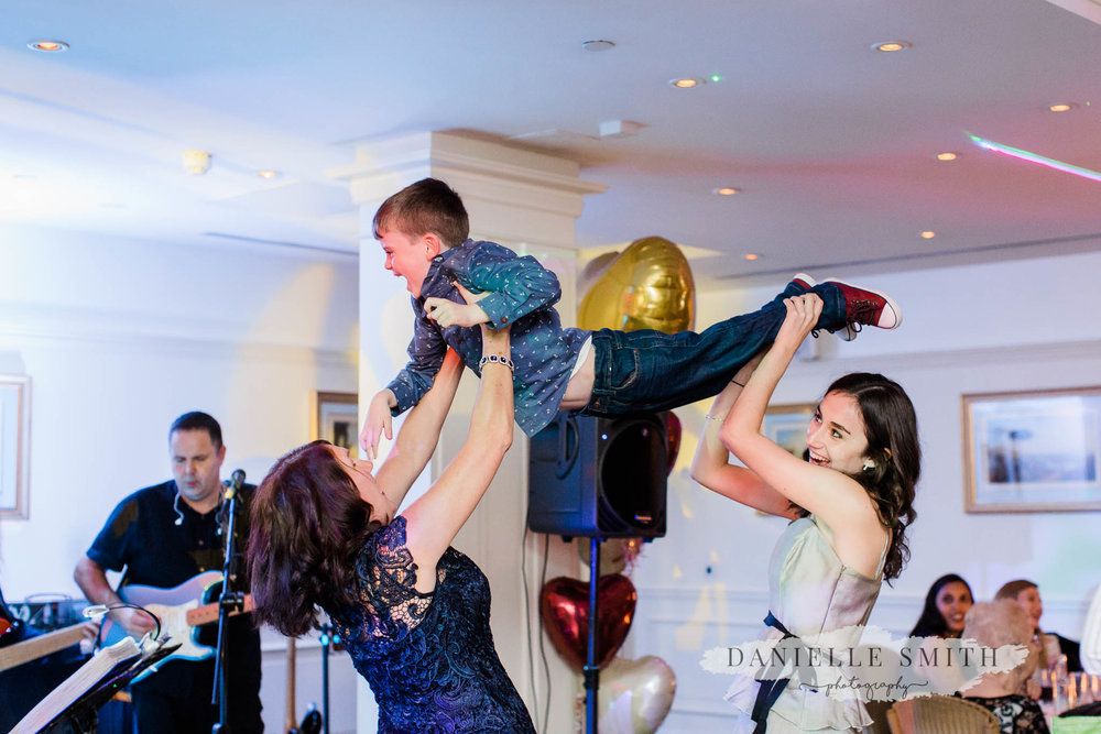 two wedding guests lifting little boy on dance floor