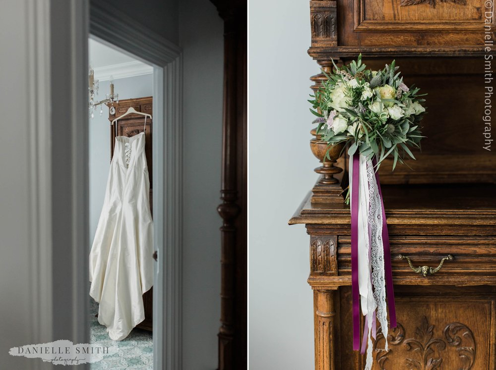 wedding dress hanging and bouquet
