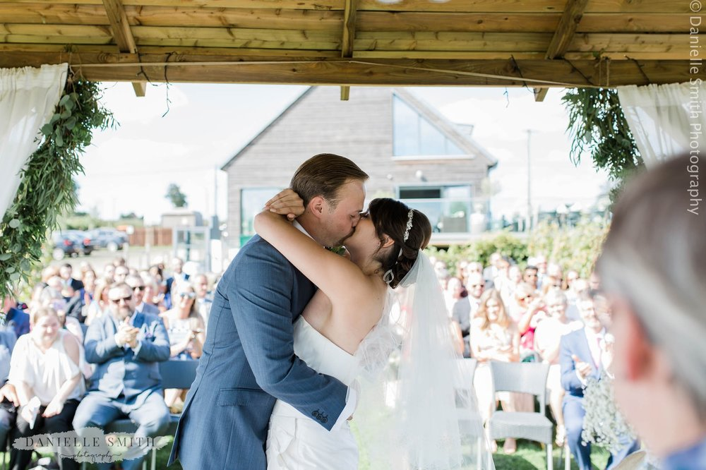 bride and groom first kiss at vineyard wedding