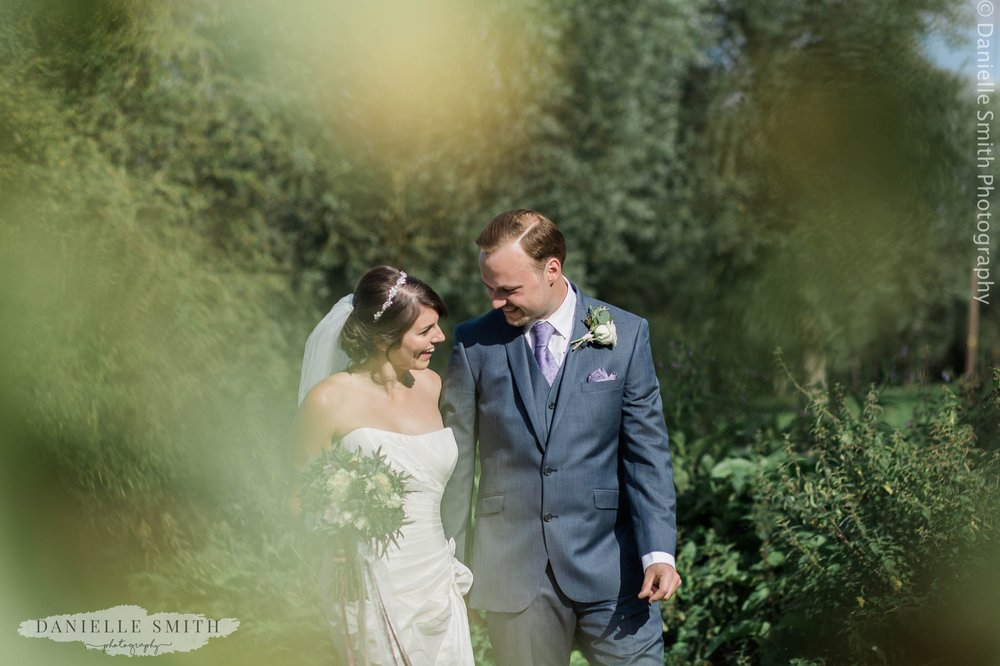 bride and groom smiling at outdoor wedding