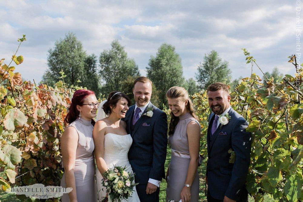 bridal party laughing in vineyard wedding