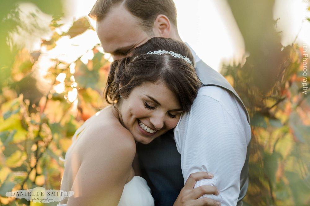 bride smiling on grooms shoulder in vineyard - essex wedding photography