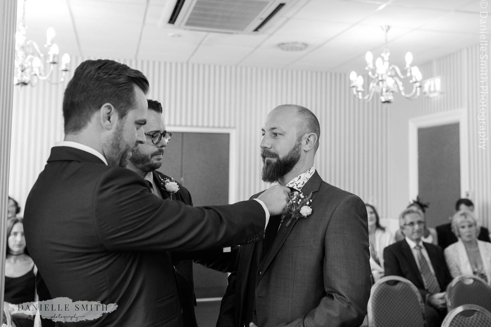 best men helping groom with his tie