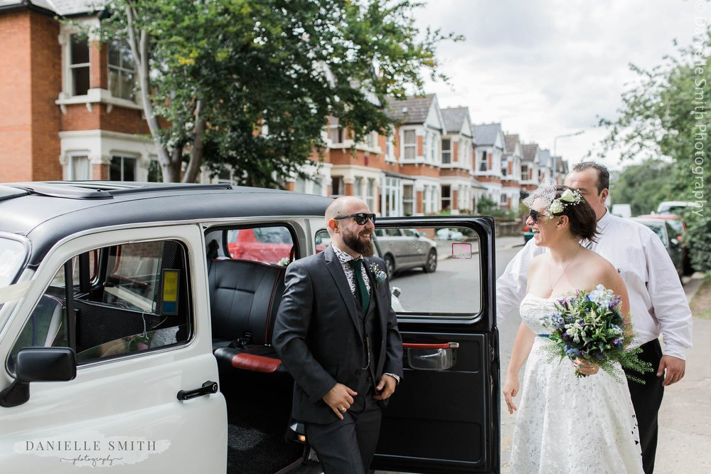 bride and groom getting out of white taxi