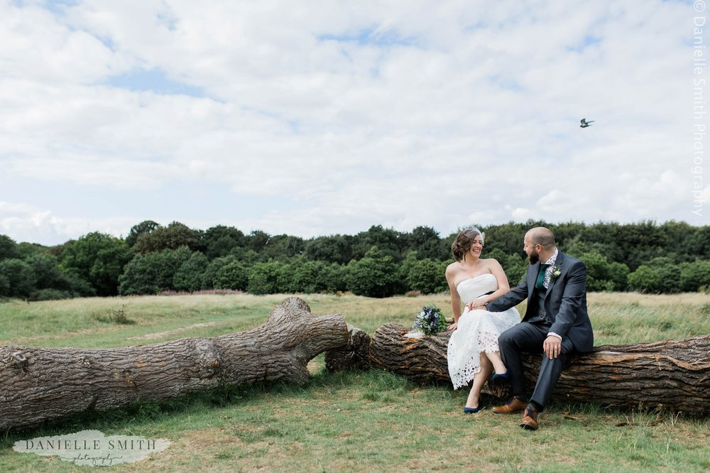 bride and groom sitting on log - east london wedding