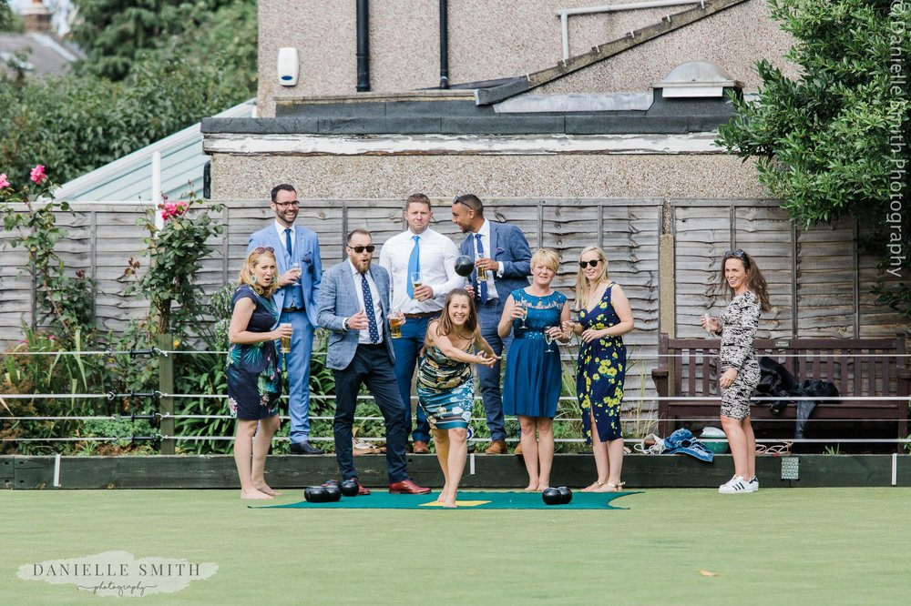 girl throwing bowls ball in air - bowls club wedding