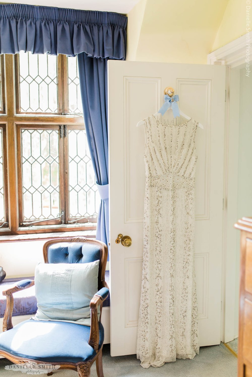 gatsby style beaded wedding dress hanging on door
