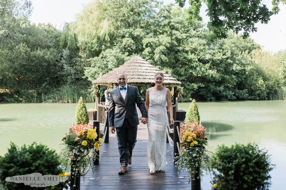 bride and groom walking down aisle over the lake - mangapp