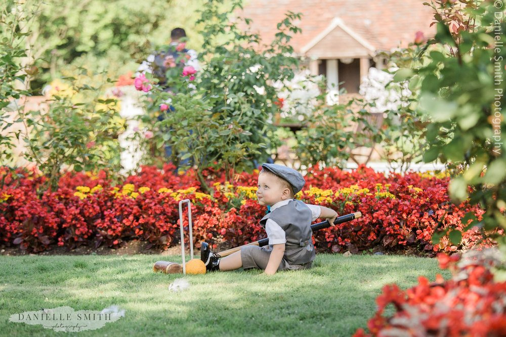 page boy sitting on floor in gardens