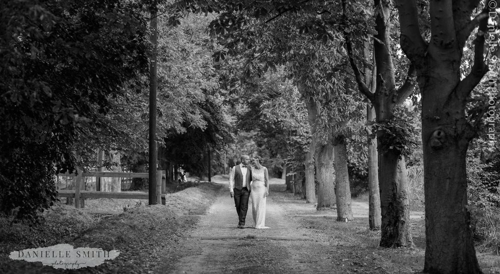 black and white bride and groom walking through trees