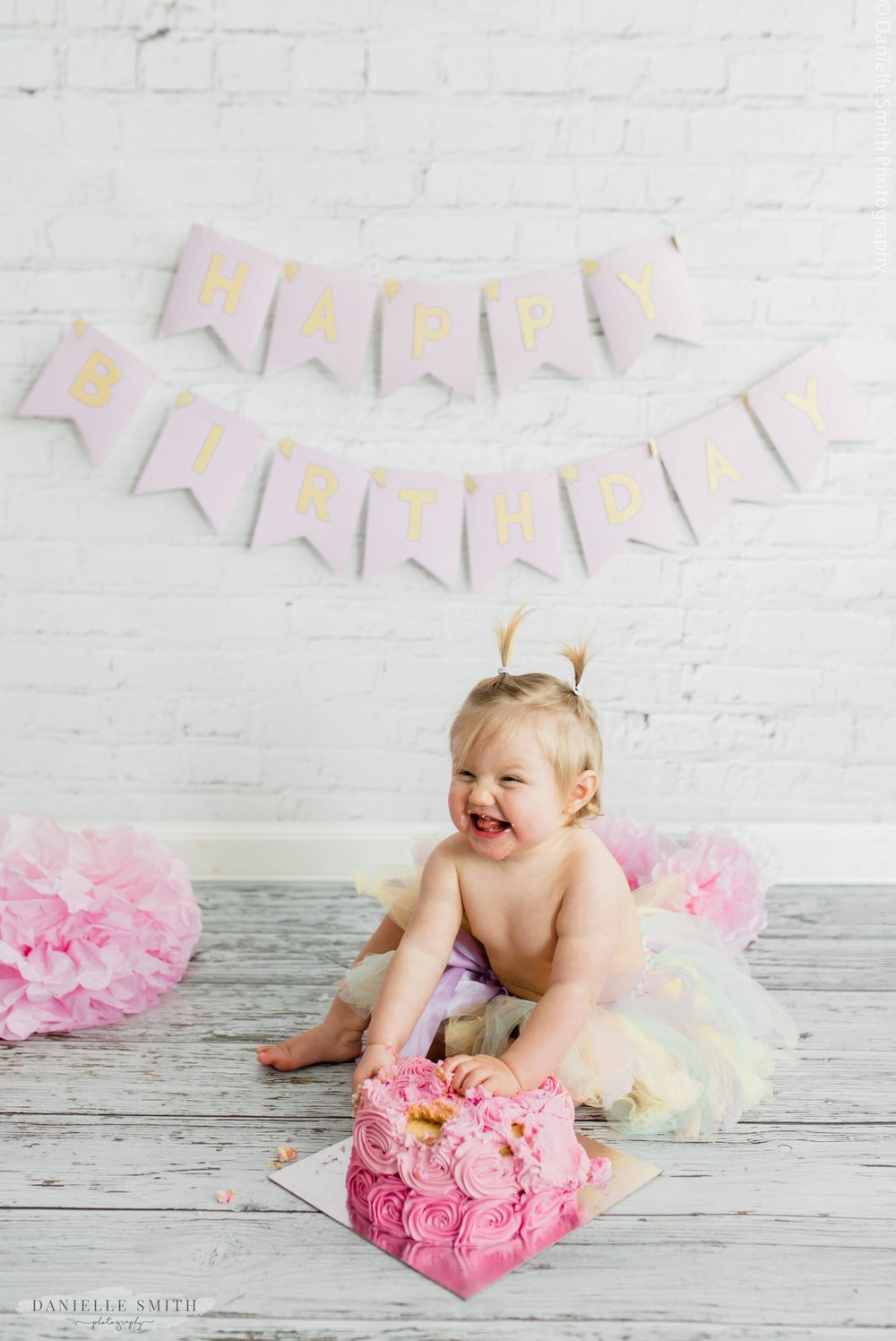 first birthday cake smash photo session girl laughing