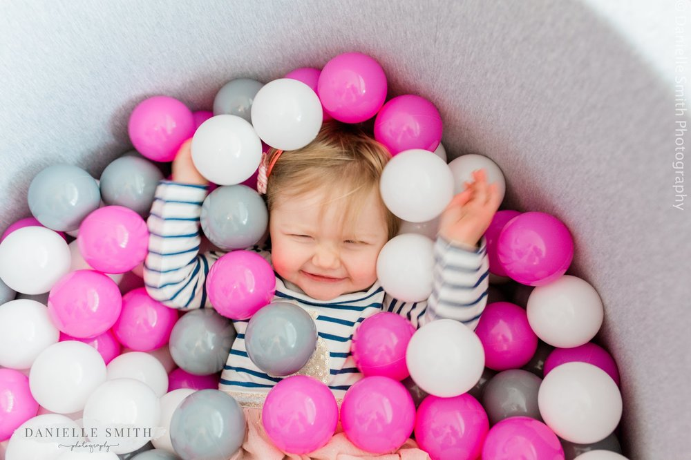 girl laying in ball pool - first birthday photos