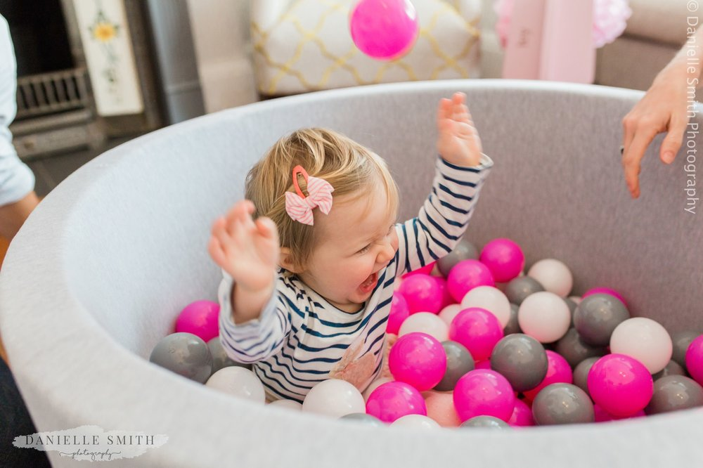 baby girl having fun splashing in her ball pool