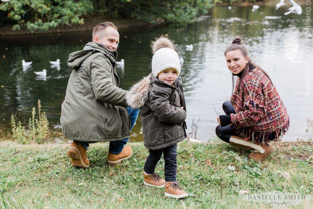 mum, dad and son feeding the ducks