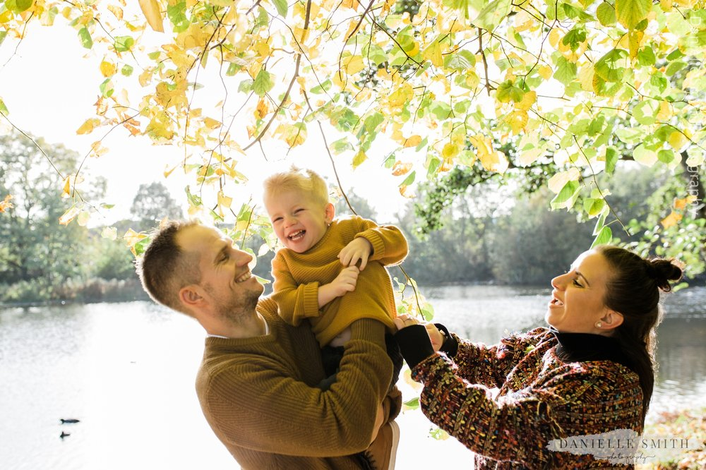 mum dad and son laughing in the park