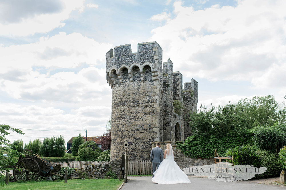 bride and groom walking towards castle - cooling castle barn