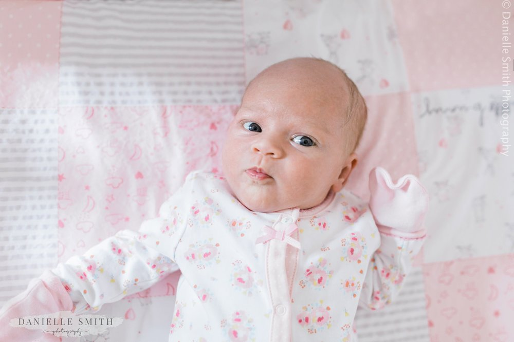 baby girl with pink patchwork blanket