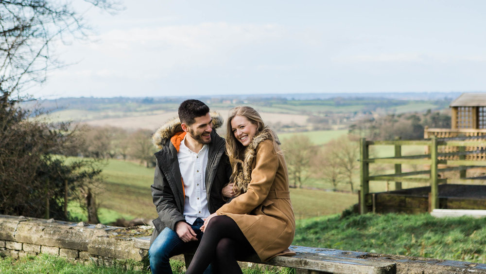 couple sitting with view across countryside behind them