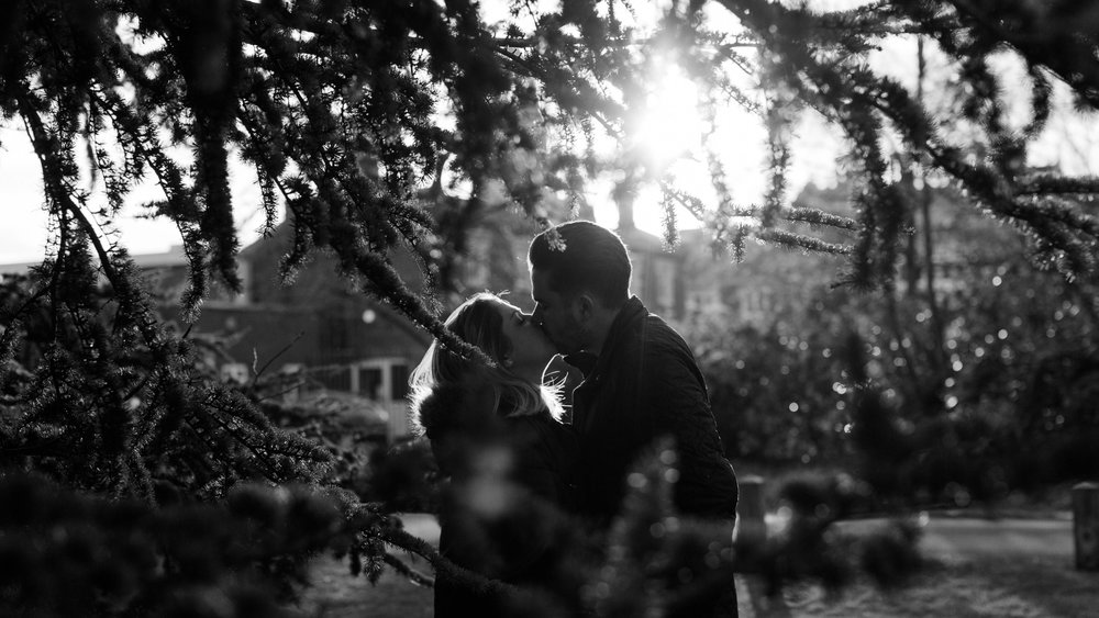 black and white photo of couple kissing through tree branches