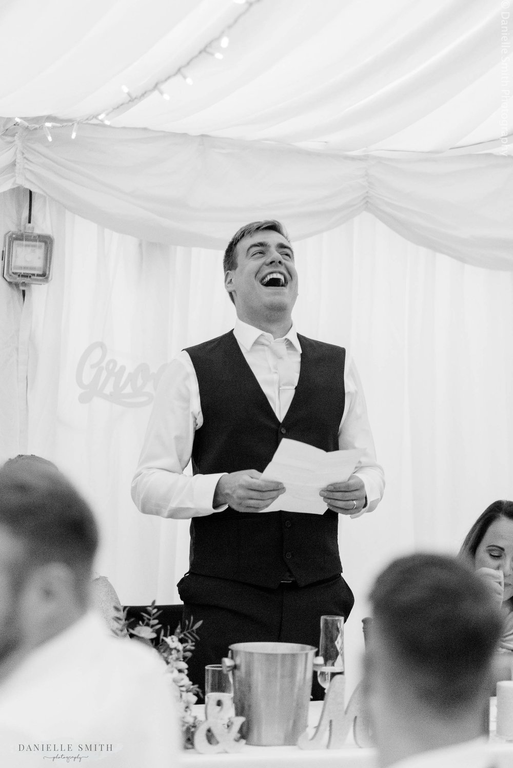 groom laughing during speech