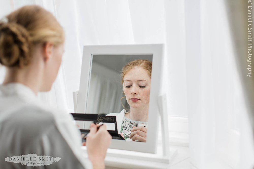 bride doing her own make up