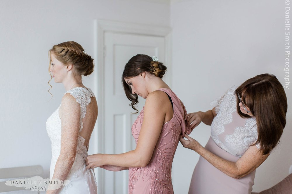bride, bridesmaid and mother of the bride doing back of dresses up