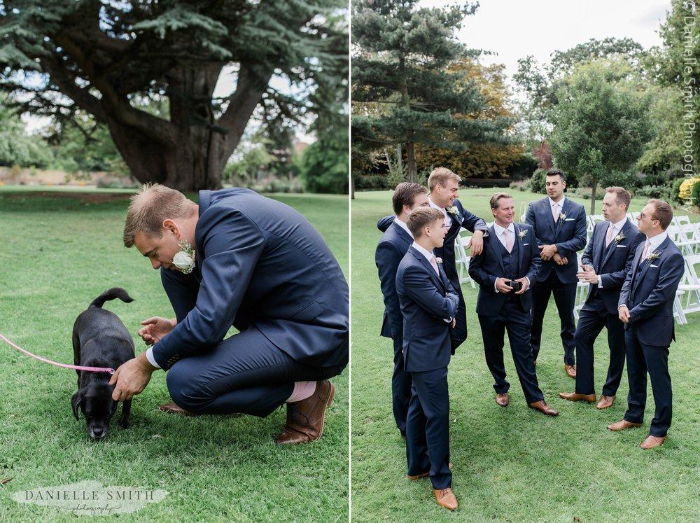 groom greeting his dog and groomsmen chatting