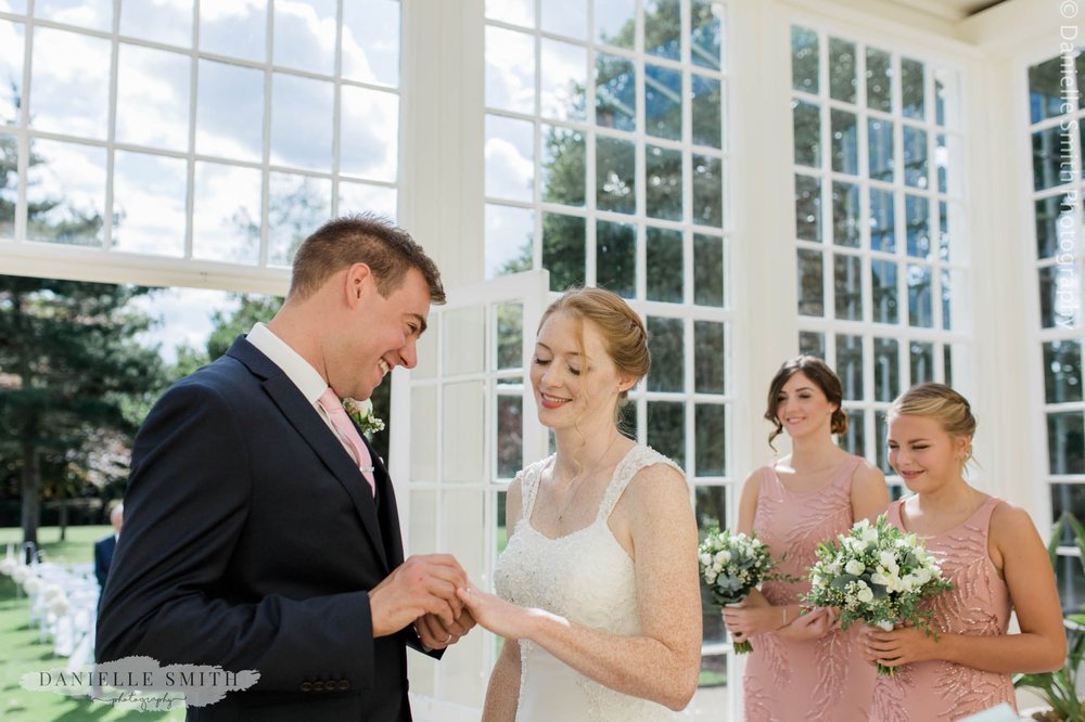 bride and groom exchanging rings- intimate garden wedding