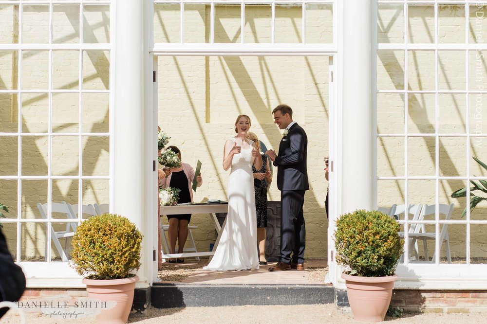 bride doing thumbs up after married - orangery wedding