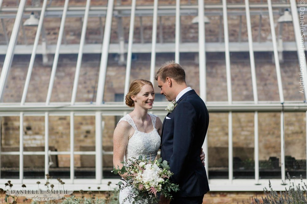 bride and groom outside glass building
