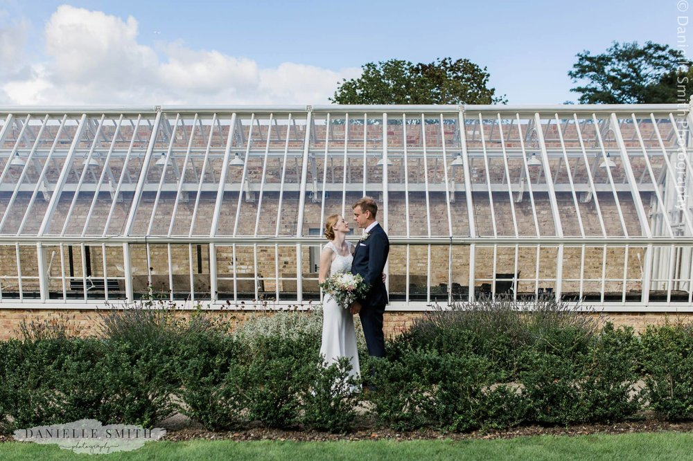 bride and groom outside glass building at Langtons