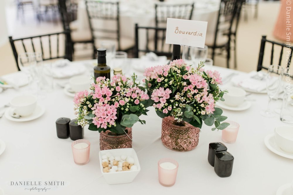 pink pots of flowers on wedding reception tables