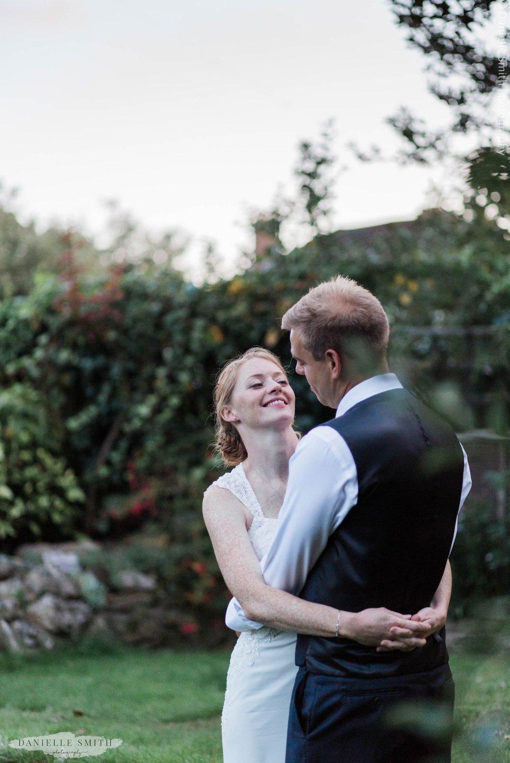 bride and groom in garden during evening