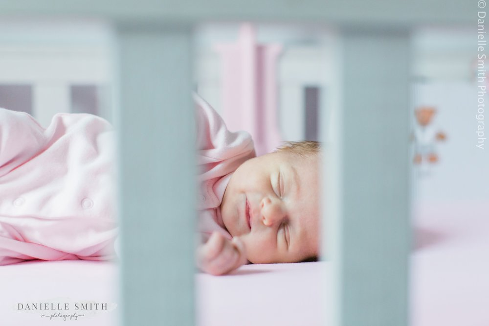 newborn baby girl laying in cot - romford newborn photography