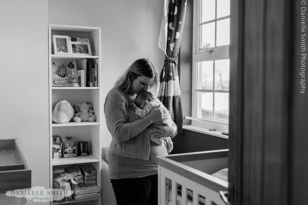mum in nursery with newborn baby boy