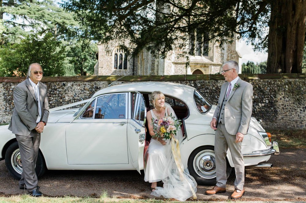 bride getting out of vintage wedding car