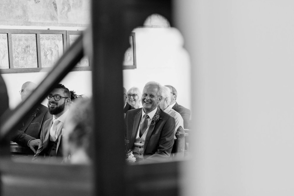 father of groom laughing in church