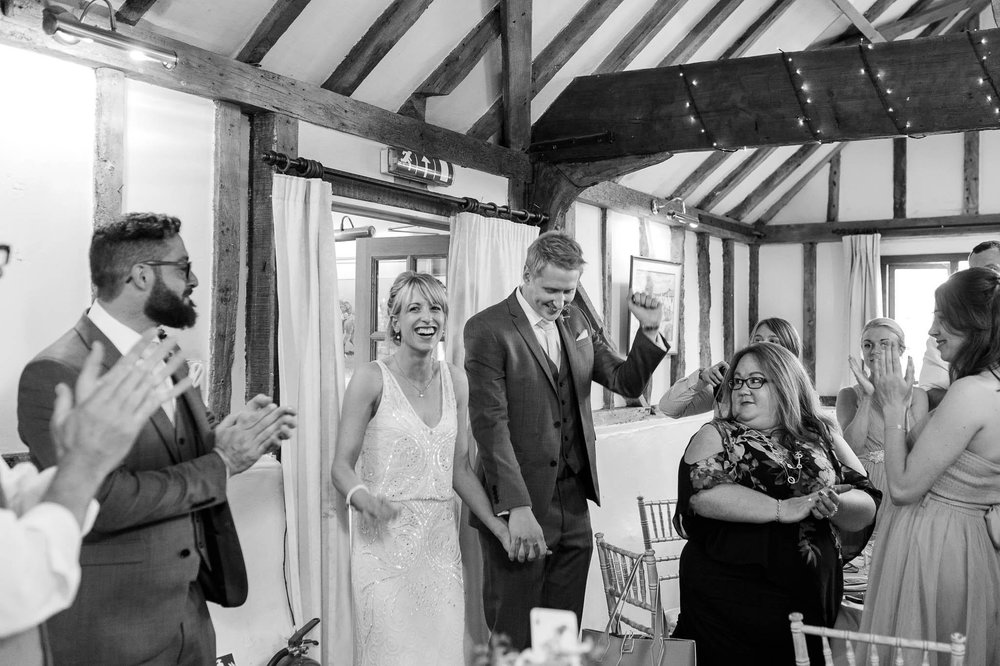 bride and groom cheering as they enter reception room
