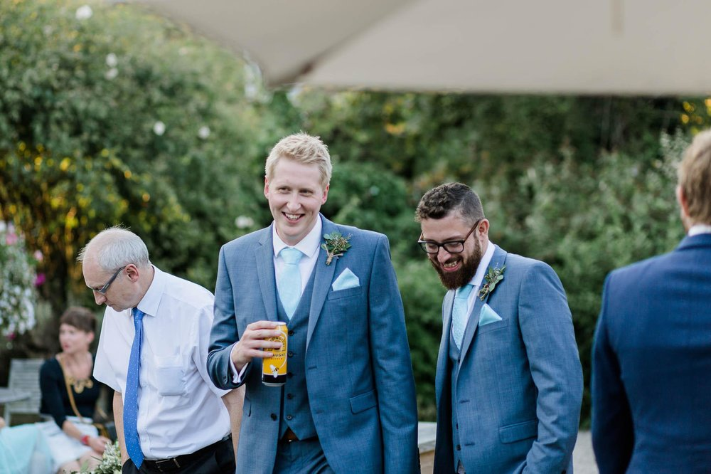 groom and best man laughing at reid rooms