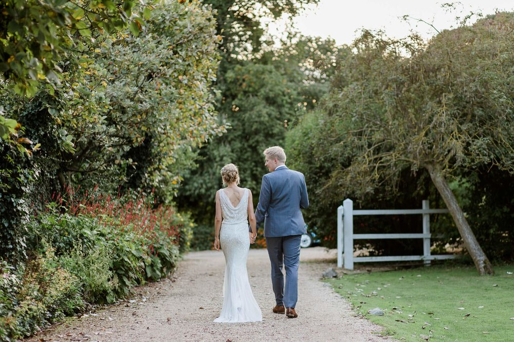 bride and groom walking off into gardens - reid rooms wedding photographer