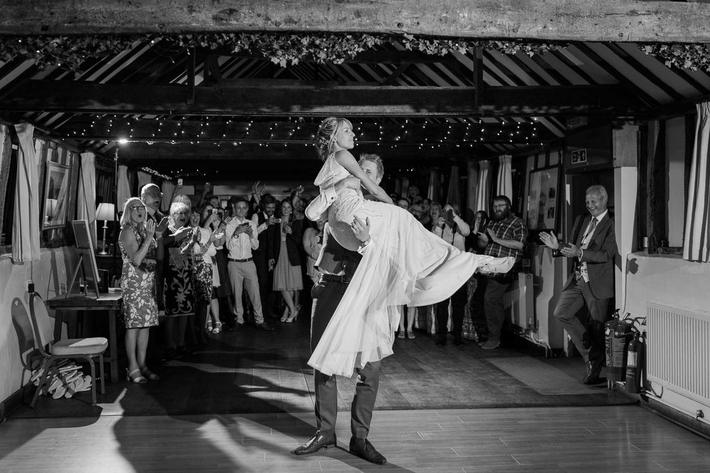groom lifting bride and spinning her for first dance
