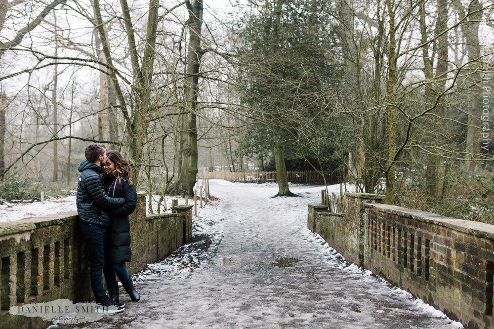 couple hugging on bridge in snow