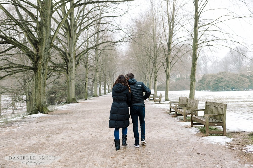 couple walking between trees in snow - pre-wedding photography hampstead heath