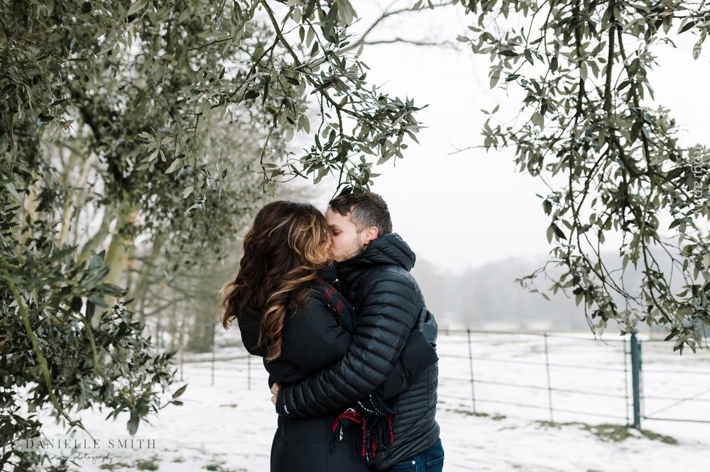 couple kissing in snowy park - pre-wedding photography hampstead heath