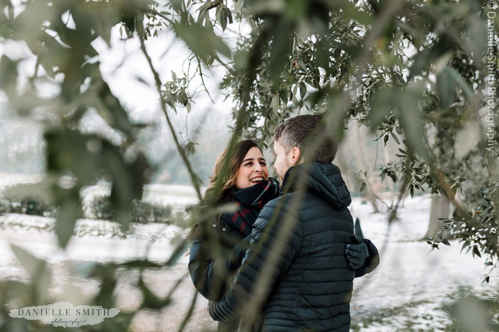 couple laughing through trees in snow