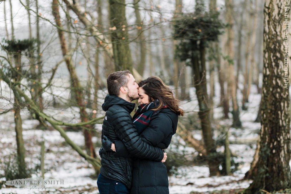 man kissing girlfriends head in snowy park - pre-wedding photography hampstead heath
