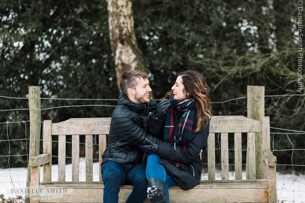 couple laughing on bench in snowy hampstead heath