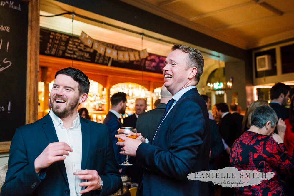 two guys laughing at pub wedding reception